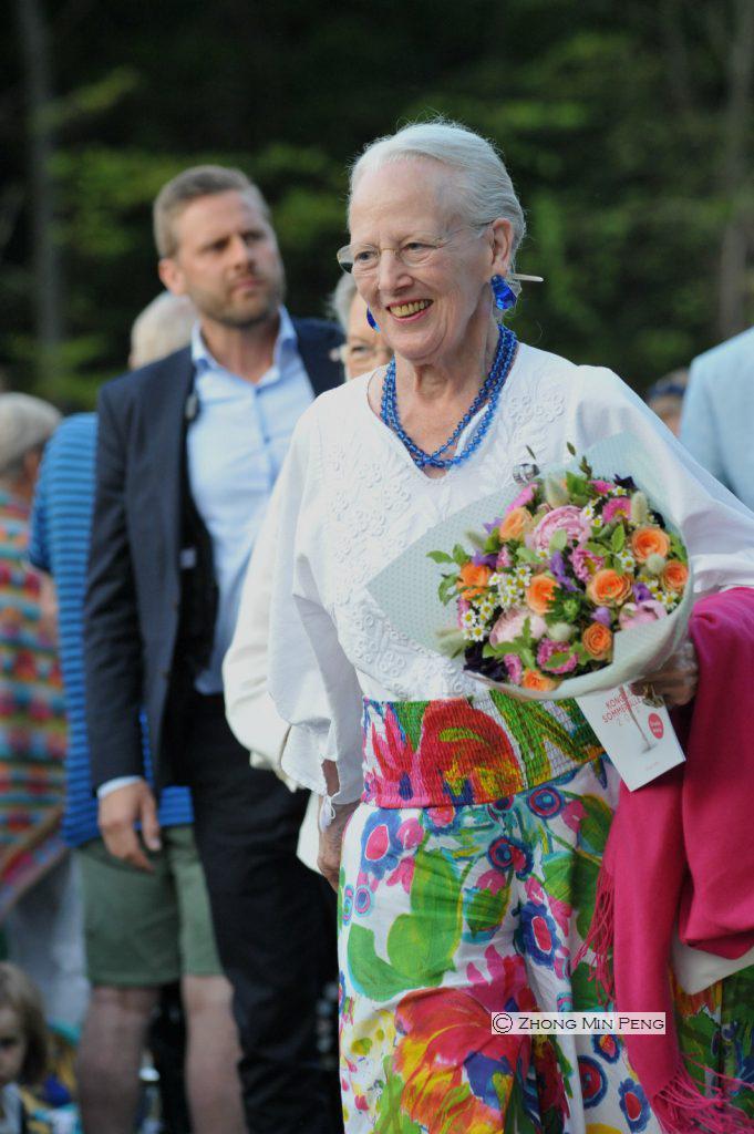 Dronningen gaar med buket blomster